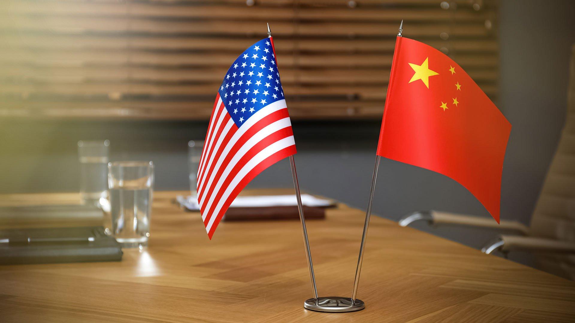 Flaggen von China und USA auf einem Schreibtisch