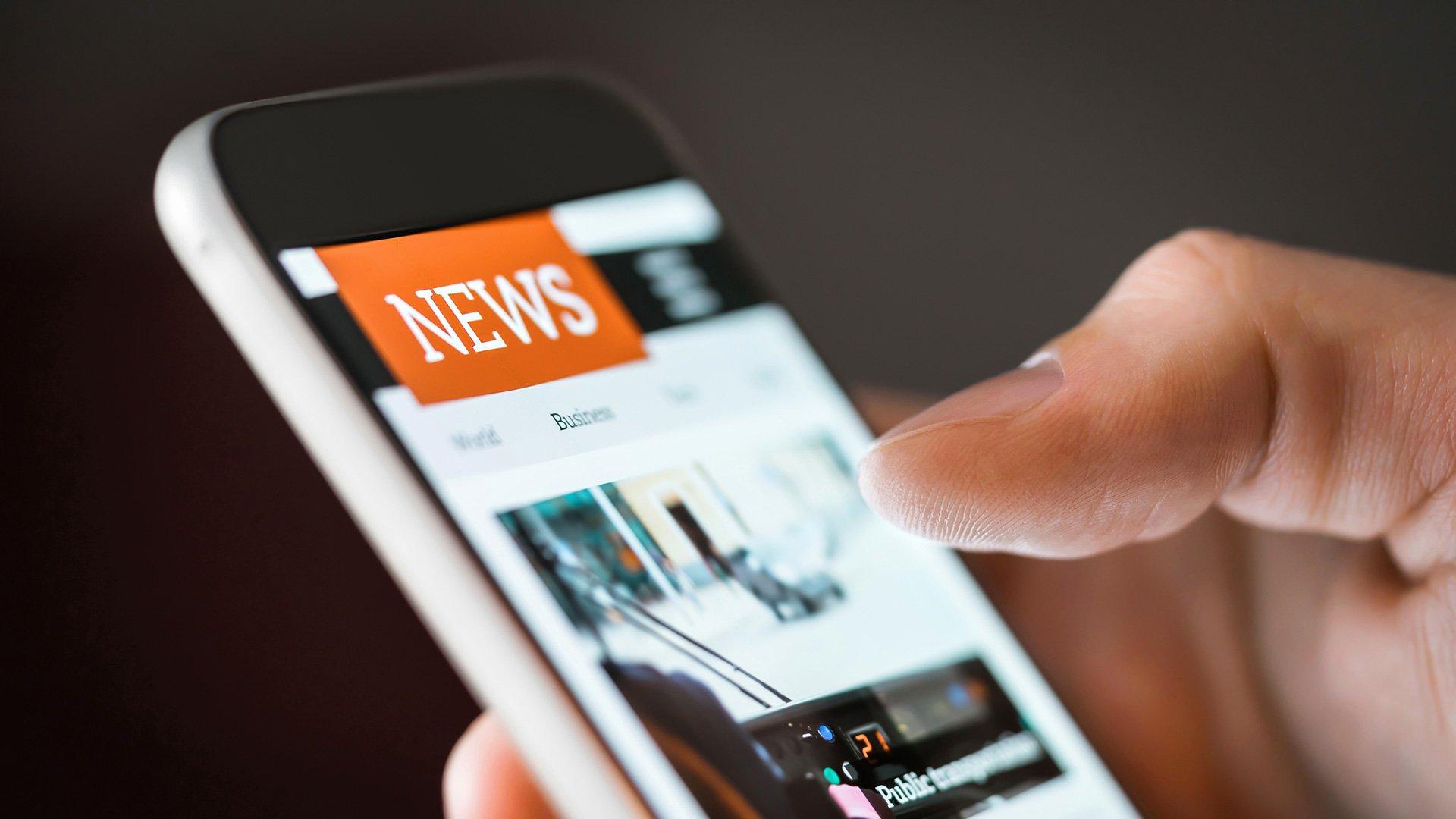 Hand hält Smartphone mit Nachrichten-Webseite
