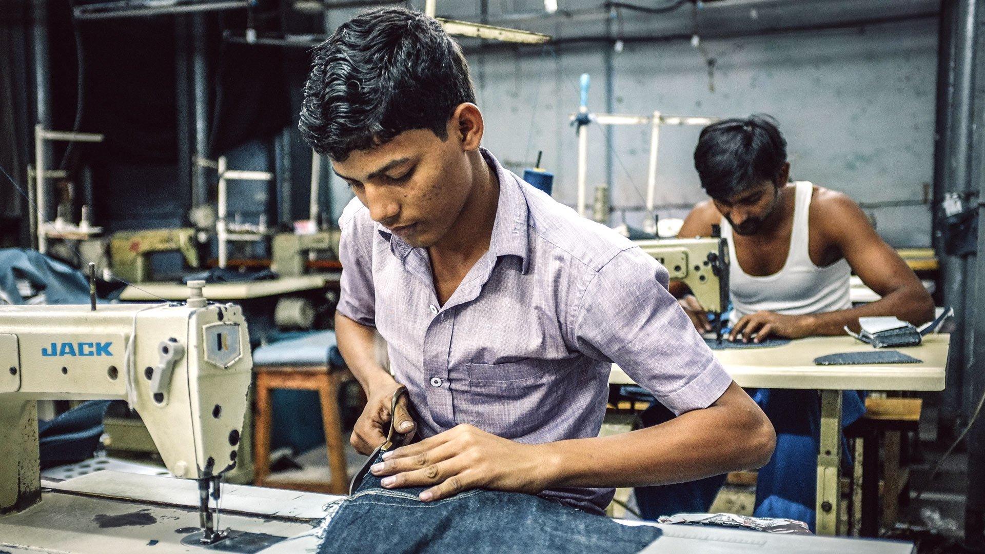 Indische Arbeiter nähen in einer Bekleidungsfabrik im Slum von Dharavi