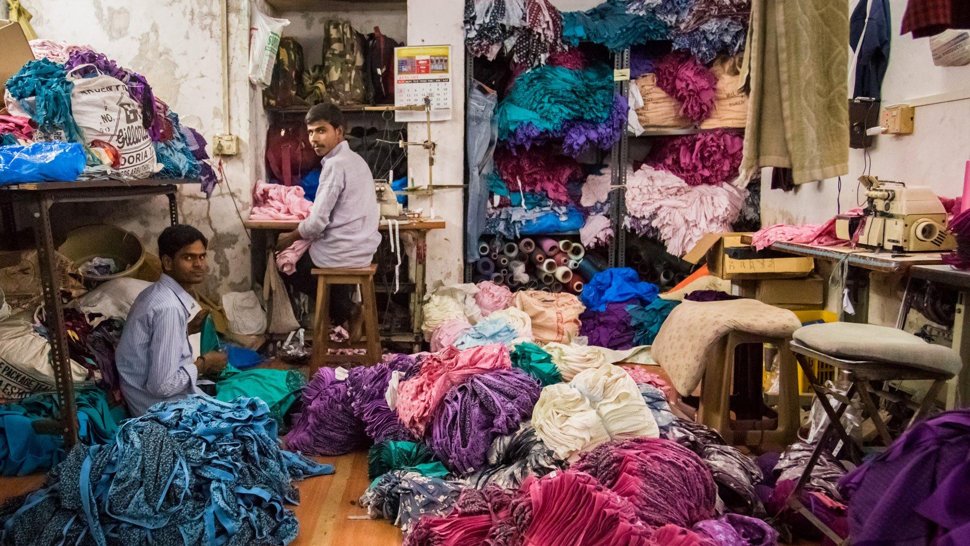 Zwei Männer arbeiten in einer kleinen Wäschefabrik im Slum von Dharavi.